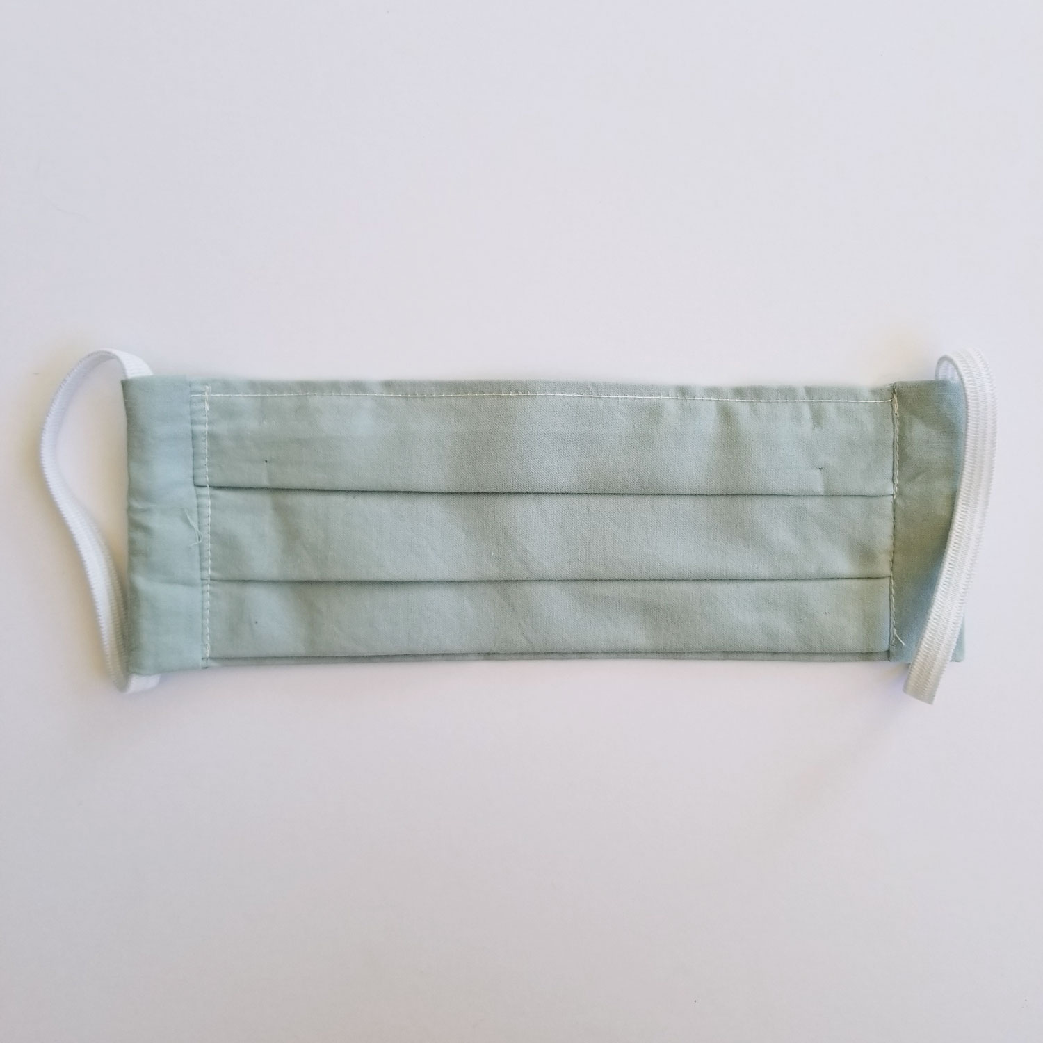 Handmade fabric mask in soft, woven green cotton