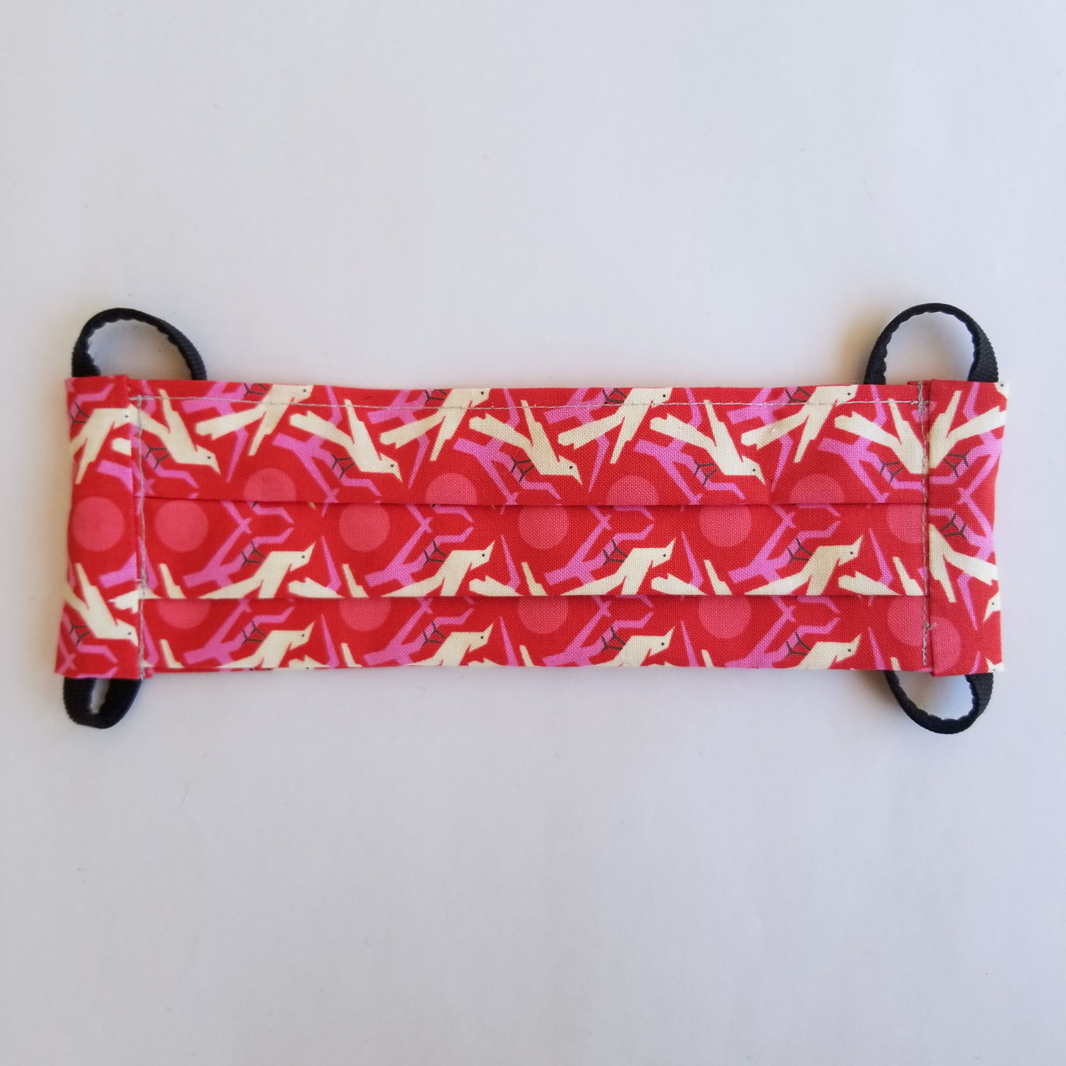 Handmade fabric mask in bright pink print with birds