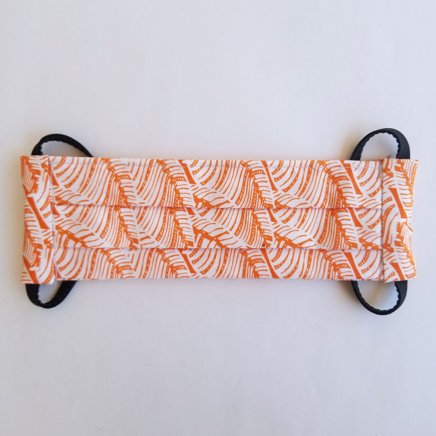 Handmade fabric mask in orange and white leaves print